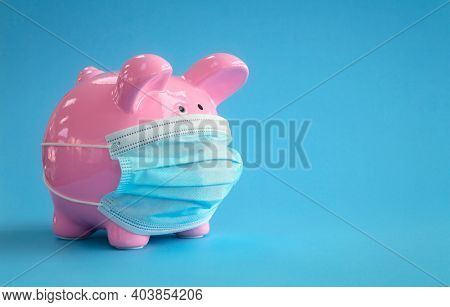 Piggy bank wearing protective medical face mask background concept for coronavirus pandemic finance cost