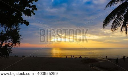 Silhouettes Of Group Of People During The Sunset In Seaside Beach. Beautiful Sunset Over The Sea Wit