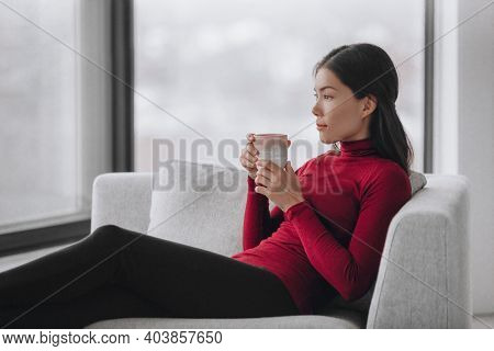 Asian woman relaxing at home during coronavirus lockdown feeling calm and serene enjoying drinking coffee alone indoors. Mental health, wellness, well-being.