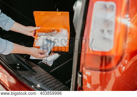 Young Woman Using Car First Aid Kit Box With Kind Of A Medical Aids, Transport Concept