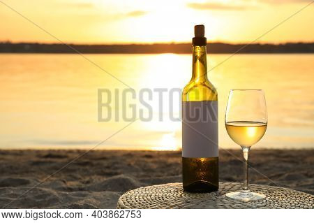 Bottle And Glass Of Delicious Wine On Riverside At Sunset