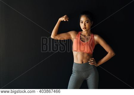 Focused Active Youthful Asian Female Athlete Looking At Camera And Showing Arm Muscles In Studio On