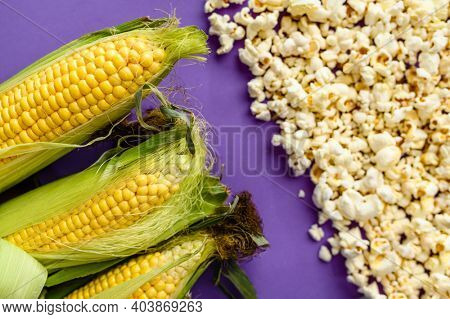 Corncobs and popcorn isolated on purple background