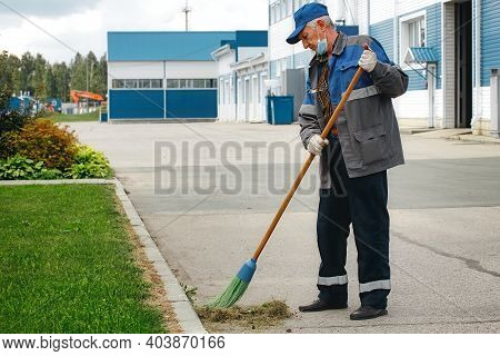 This Is An Elderly Janitor With A Broom In A Medical Mask On The Street Sweeping The Territory. An O