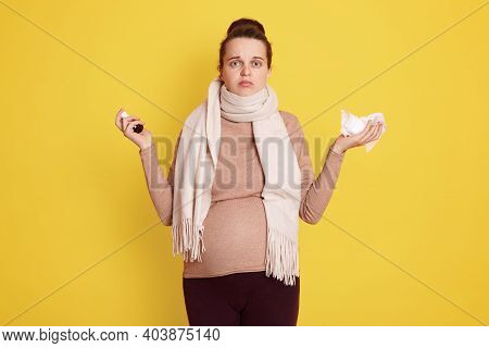 Young Beautiful Pregnant Girl In Beige Sweater And Scarf Uses Remedy For Nasal Congestion, Upset Exp