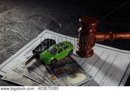 Wooden Judge Gavel And Green Toy Car With Keys On Money. Symbol Of Law, Justice And Car Auction