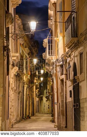 Narrow street in Ortygia, the historical part of Syracuse at night, Sicily, Italy