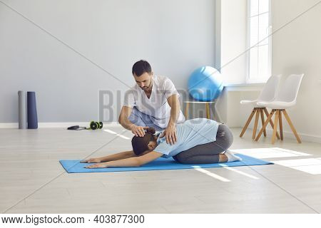 Licensed Chiropractor Or Physiotherapist Helping Woman To Do Medical Exercise On Sports Mat