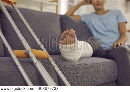 Close Up Of A Crutches And A Broken Leg In A Plaster Cast Of A Woman Sitting On A Sofa And Resting.