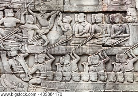 Bas-relief on stone wall of Prasat Bayon temple. Carvings of people in boats,  Angkor Wat (Angkor Thom), Siem reap, Cambodia, Indochina. UNESCO world heritage Site