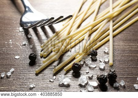 Spaghetti, A Fork, Salt And Pepper On An Old Wooden Table