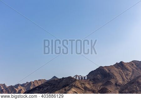 Hajar Mountains Range In Hatta, With Large Hollywood Style Hatta Sign On Top Of The Hill, United Ara