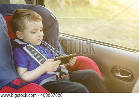 Portrait Of A Bored Little Boy Sitting In A Car Seat. Safety Of Transportation Of Children.