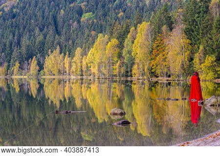 Red Lady And Autumn Trees Reflecting In Water Lake. Saint Anne Lake Is The Only One Crater Lake From
