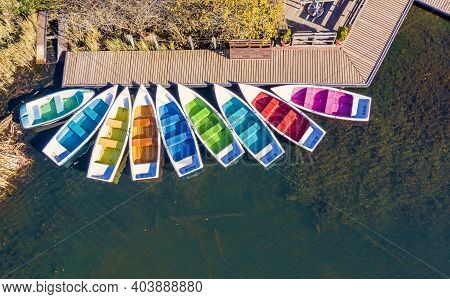 Above View Of Colored Boats Docked. Red Lake Is A Natural Dam Lake In Romania Located In The North-e