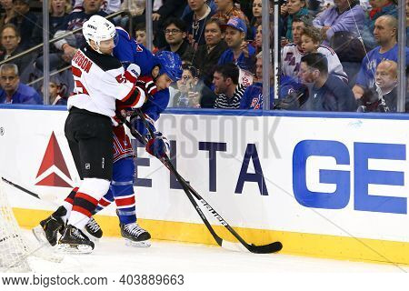 NEW YORK-APR 27: New Jersey Devils defenseman Adam Larsson (5) and New York Rangers left wing Taylor Pyatt (14) battle for the puck at Madison Square Garden on April 27, 2013 in New York City.