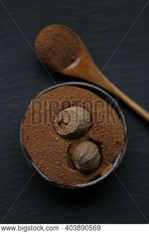 Nutmeg.whole And Grated Nutmeg In A Ceramic Black Cup And Spoon On A Black Slate Background. And Her