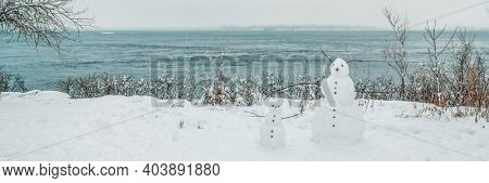 Winter scenery fun outdoor activity for kids, building snowman in snow in Quebec, Canada. Nature fun banner. Two snowmen in front of water.