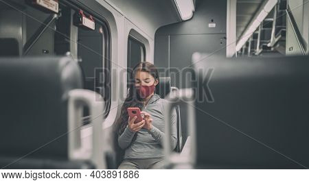 Train passenger using mobile phone during travel commute wearing face mask for coronavirus pandemic. Panoramic banner of people lifestyle commuting after work at night.