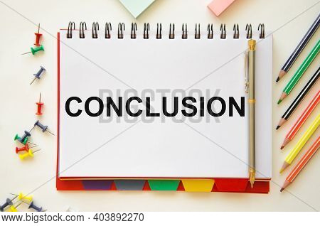 The Word Conclusion Is Written On A White Notebook That Lies On A White Table Near Stickers And Colo