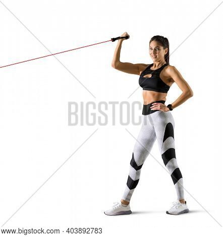 Fitness woman performs exercises with resistance band. Fitness model in sportswear isolated on white background