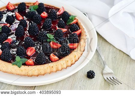 Summer Berry Tart With Blackberries And Strawberries On A Wooden Table.
