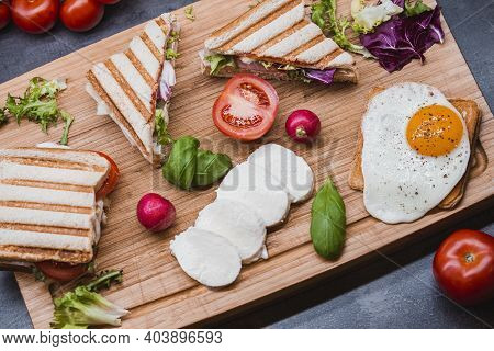 Sandwiches On Wooden Cutting Boards. Club Sandwich Panini With Ham, Tomato, Cheese, Basil, Mozzarell