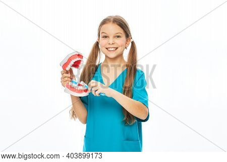 Smiling Girl In A Blue Uniform Showing How To Properly Brush Her Teeth Using An Anatomical Model Of