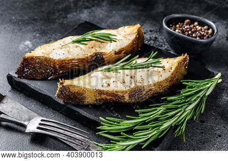 Halibut Fish Steak With Rosemary. Black Background. Top View