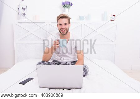 Happy Man With Laptop Hold Tea Cup To Stay Hydrated Being Sick In Bed At Home With Covid-19, Hydrati