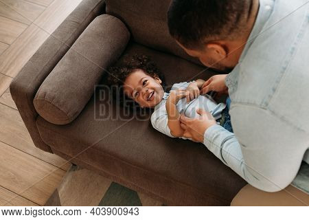 High-angle View Of A Father Tickling His Son. Happy Little Boy Lying On A Sofa.