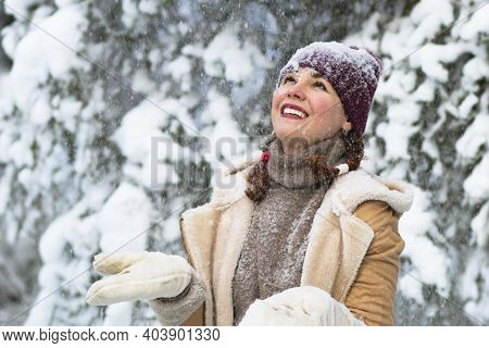 Happy Woman On The Background Of The Forest, Snow Falls On The Girl, The Female Smiles In Winter.
