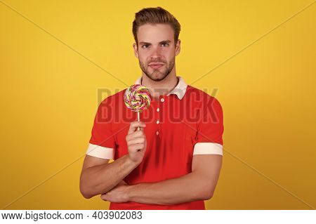 Taste The Rainbow. Man Candy Yellow Background. Handsome Guy Hold Candy On Stick. Candy Shop. Lollip