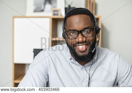Young And Handsome African-american Employee Wearing Glasses, Headset With A Microphone, Working In