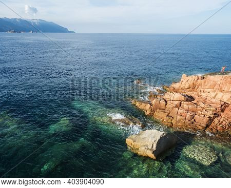 Red Rocks Called Rocce Rosse At Mediterranean Sea Coastline In Arbatax With Two Boys Fishing. Tortol
