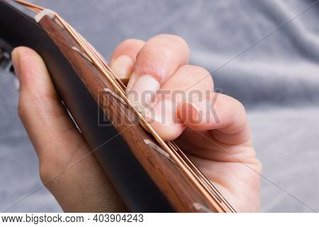 Fingers Clamping Chord On Guitar Strings Close Up