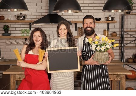 Family Restaurant Concept. Best Cooking Team. Mom Dad And Daughter Aprons In Kitchen. Lunch Time. Fa