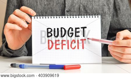 A Man In A White Shirt Holds A Piece Of Paper With The Text: Budget Deficit. Multicolored Markers An