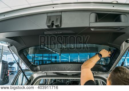 Car Window Tinting. Process Of Installation Window Tint In Car Detailing Studio Garage By Profession