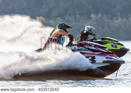 Krasnodar, Russia - October 24, 2020: Jet Ski Racers Drive Watercrafts Splashing In Sunset While Rac