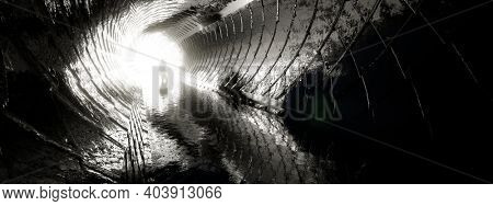 Concept or conceptual dark tunnel with a bright light at the end or exit as metaphor to success, faith, future or hope, a black silhouette of walking man to new opportunity or freedom 3d illustration