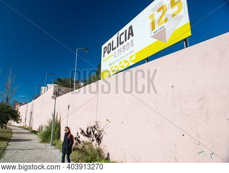 Lisbon, Portugal - Feb 10, 2018: Lonely Woman Near Tall Stone Fence With Policia Lisboa Banner Celeb