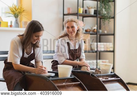 Two Women Make Pottery On A Pottery Wheels, Shaping Clay By Their Hands, Close Up. Pottery Craft Wor