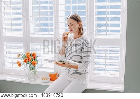 Beautiful Happy Middle Age Woman Sitting On Windowsill At Home And Reading Book. Young Woman With Sh