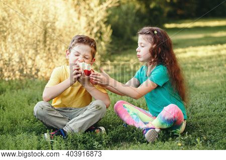Caucasian Children Boy And Girl Siblings Sitting Together Sharing Apple. Two Kids Brother And Sister