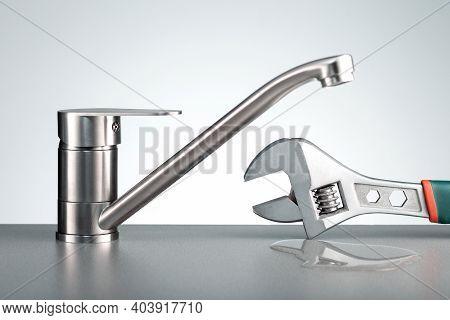 Repair Plumbing Background. Faucet With Leak Water And Tool.