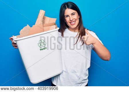 Young beautiful woman recycling cardboard on wastebasket to care environment smiling happy and positive, thumb up doing excellent and approval sign