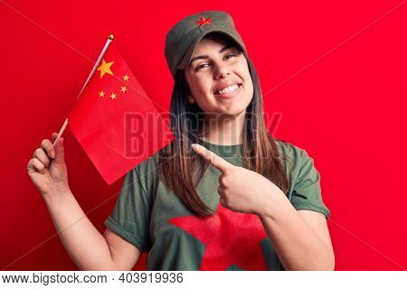 Beautiful patriotic woman wearing t-shirt with red star communist symbol holding china flag smiling happy pointing with hand and finger