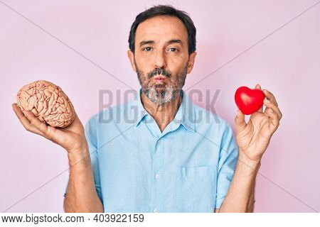 Middle age hispanic man holding brain and heart puffing cheeks with funny face. mouth inflated with air, catching air.