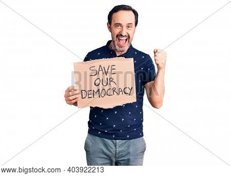 Middle age handsome man holding save our democracy cardboard banner screaming proud, celebrating victory and success very excited with raised arms
